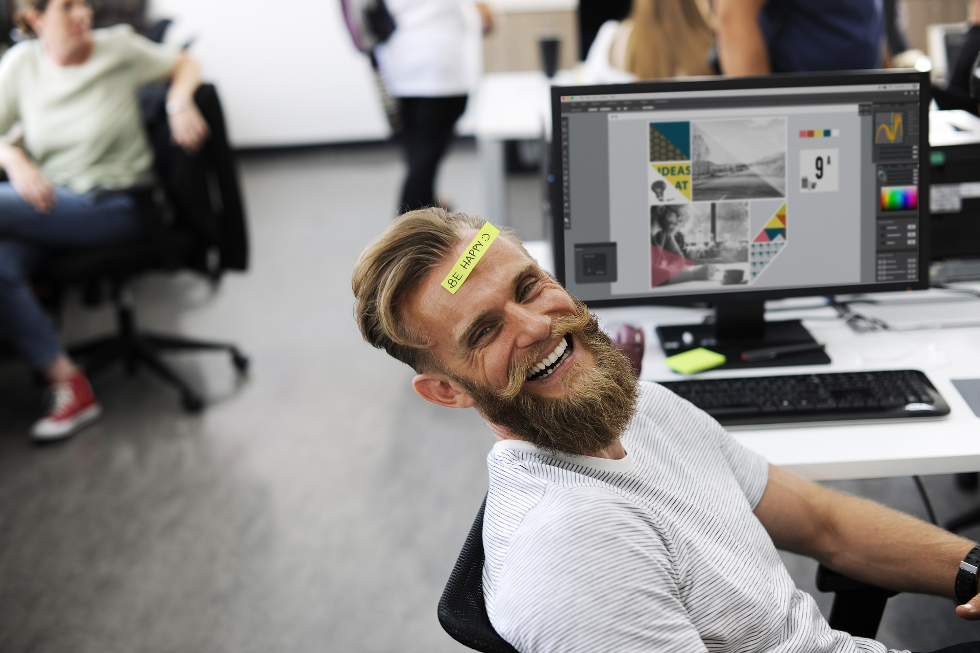 Homme avec un post-it sur le front riant devant son ordinateur